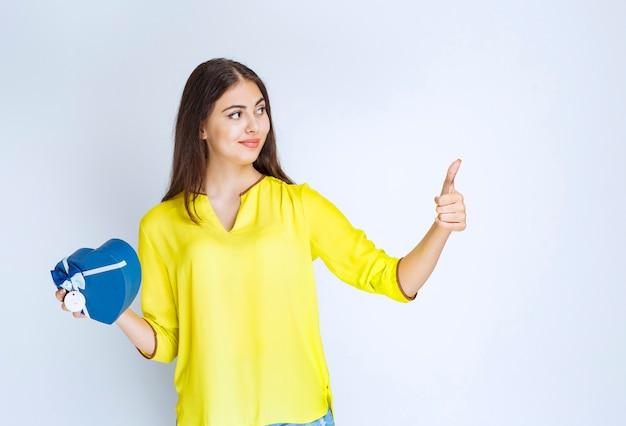 Dziewczyna trzyma pudełko na prezent w kształcie niebieskiego serca i pokazując kciuk do góry.