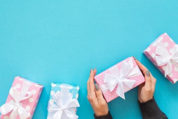 Dziewczyna trzyma pudełko, różowe i niebieskie pudełka na prezenty w kropki z białą wstążką i kokardą na niebieskim tle, płaski widok, widok z góry, urodziny lub walentynki