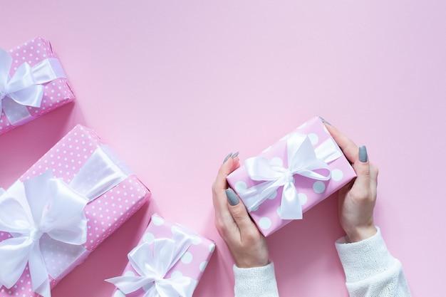 Dziewczyna trzyma pudełko, różowe pudełka w kropki z białą wstążką i kokardą na różowym tle