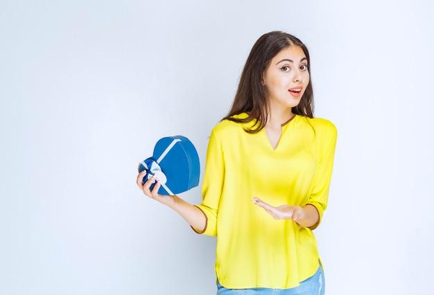 Dziewczyna trzyma pudełko upominkowe w kształcie niebieskiego serca i dzwoni do kogoś, aby je zaprezentować.