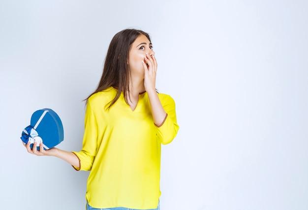 Dziewczyna trzyma pudełko w kształcie niebieskiego serca i wygląda na zdziwioną i przerażoną.
