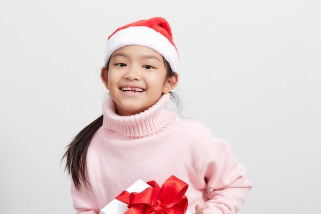 Dziewczyna trzyma pudełko w sweter i kapelusz santa