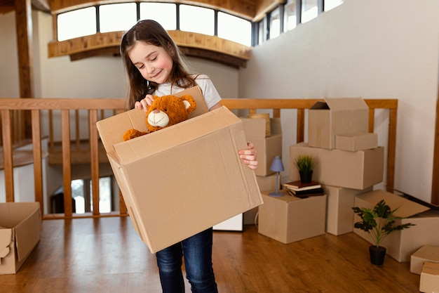 Dziewczyna trzyma pudełko z zabawkami średnim strzałem