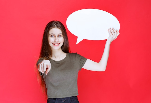 Dziewczyna trzyma pustą owalną tablicę informacyjną i wskazując na coś.