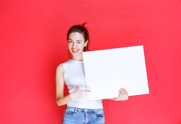 Dziewczyna trzyma pusty kwadrat ideaboard do burzy mózgów.