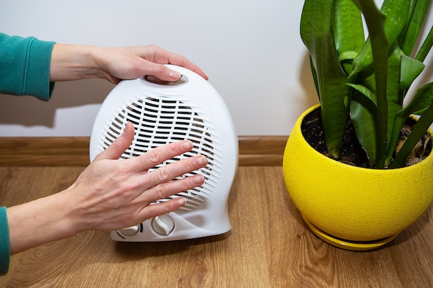 Dziewczyna trzyma ręce przy plastikowej nagrzewnicy i ogrzewa dłonie, regulując temperaturę w domu, przepływ ciepła.