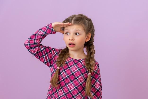 Dziewczyna trzyma rękę przy czole i patrzy w dal.