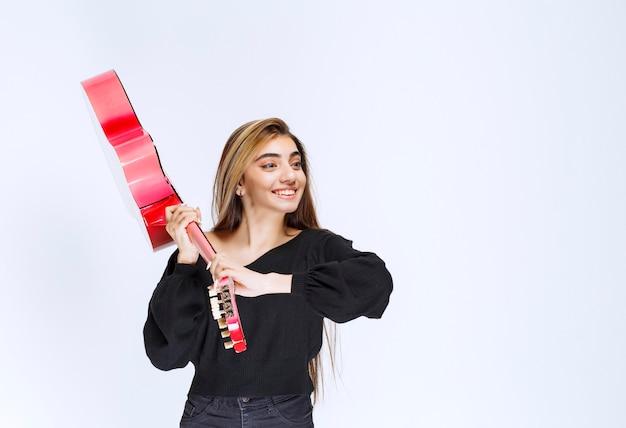 Dziewczyna trzyma różową gitarę za rączkę, żeby wszystko zepsuć.