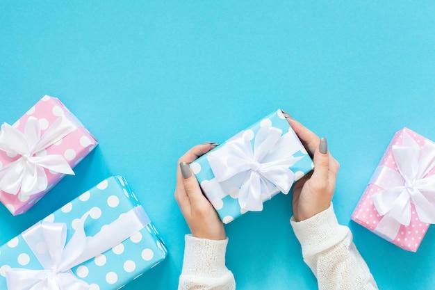 Dziewczyna trzyma różowe i niebieskie pudełka na prezenty w kropki z białą wstążką i kokardką
