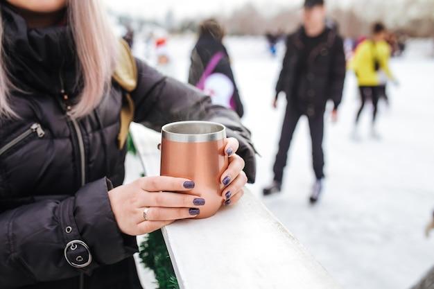 Dziewczyna trzyma różowy kubek termiczny z gorącą herbatą na lodowisku