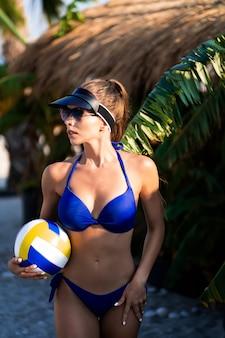 Dziewczyna trzyma siatkówkę na plaży. sportowe szczęśliwa kobieta w modnym niebieskim seksownym stroju kąpielowym, ciesząc się słońcem ćwiczeń. zdrowy tryb życia. doskonałe kształty ciała fitness.
