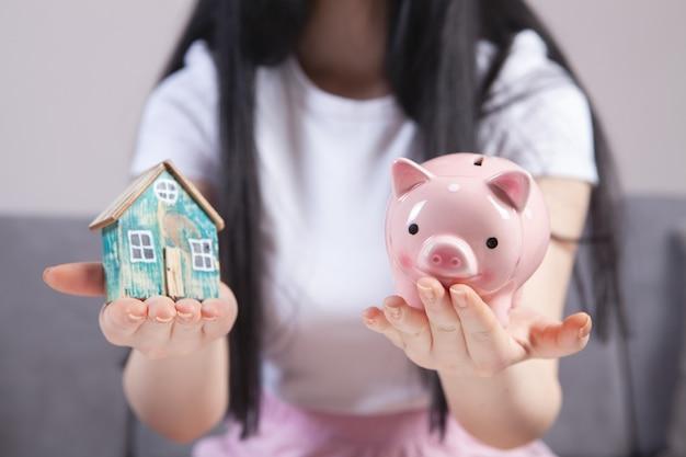 Dziewczyna trzyma skarbonkę i model domu