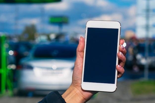 Dziewczyna trzyma smartfon w dłoniach. makieta telefonu z białym ekranem na tle samochodu elektrycznego na stacji ładującej.