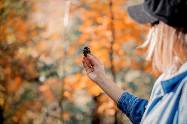 Dziewczyna trzyma sosnowego rożek na lasowym tle