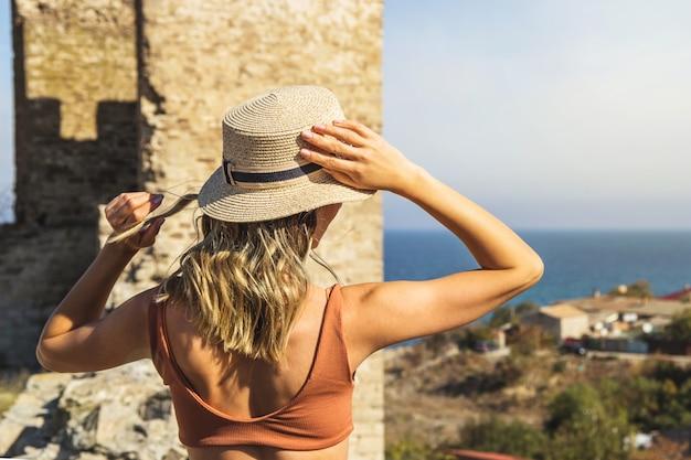 Dziewczyna trzyma swój letni słomkowy kapelusz w podróż do morza.