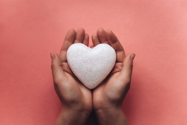 Dziewczyna trzyma symbol w kształcie serca.
