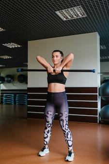 Dziewczyna trzyma sztangę. portret silny sportowy kobieta robi ćwiczenia z barem ciała w siłowni