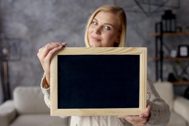 Dziewczyna trzyma tablicę kredową w mieszkaniu. copyspace.