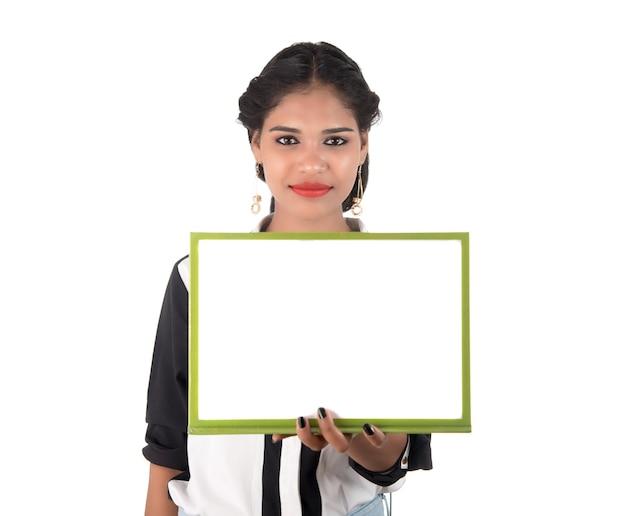 Dziewczyna trzyma tablicę pusty biały znak na białej ścianie. na białym tle portret