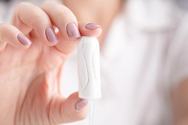 Dziewczyna trzyma tampon podczas cyklu miesięcznego. młoda kobieta ręce trzyma miesiączki bawełny tampon