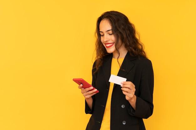 Dziewczyna trzyma telefon i kartę kredytową dokonuje płatności online