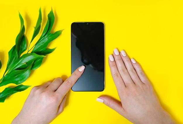 Dziewczyna trzyma telefon w dłoni. przerzucanie stron. wskazując na telefon. kwiaty. jasne żółte tło. miejsce na napis. leżał na płasko.