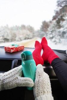 Dziewczyna trzyma termos, siedząc w samochodzie zimą, w zimowym lesie. koncepcja podróży, podróży i zimy.