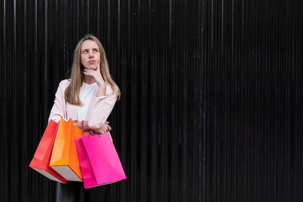 Dziewczyna trzyma torby na zakupy z ręką pod brodą