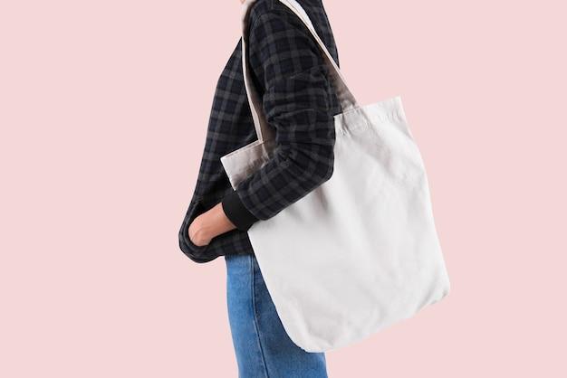 Dziewczyna trzyma torby płótno tkaniny do makiety pusty szablon na białym tle na szarym tle.