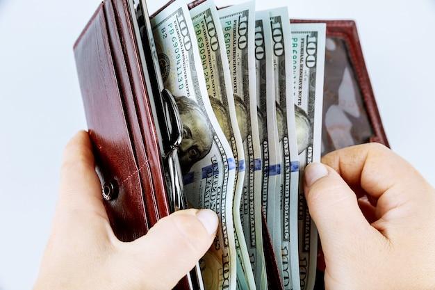 Dziewczyna trzyma torebkę z banknotami stu dolarowymi na szarym tle.