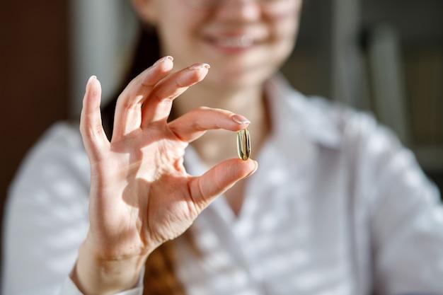 Dziewczyna trzyma w dłoni kapsułkę oleju z ryb. kapsułki omega-3 na stole iw dłoni lekarza.