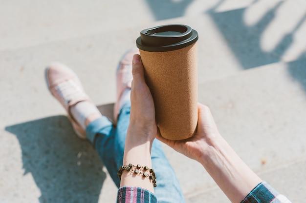 Dziewczyna trzyma w dłoni kubek termiczny z kawą.