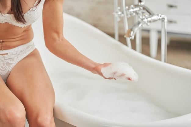Dziewczyna trzyma w dłoni piankę mydlaną