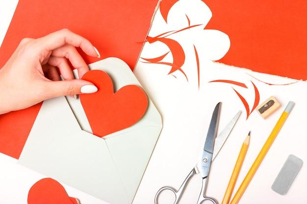 Dziewczyna trzyma w dłoni serce wykonane z czerwonego kartonu. przygotowanie listu uznania na walentynki. układ widoku z góry