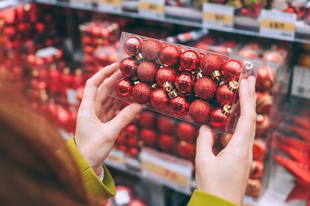 Dziewczyna trzyma w dłoniach ozdobne czerwone kulki do dekoracji świąt bożego narodzenia i nowego roku