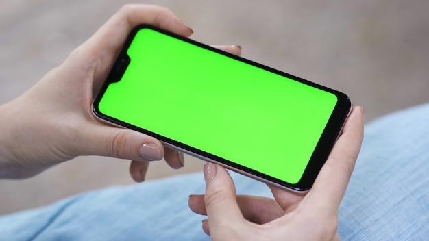 Dziewczyna trzyma w dłoniach smartfon i przewija wiadomości
