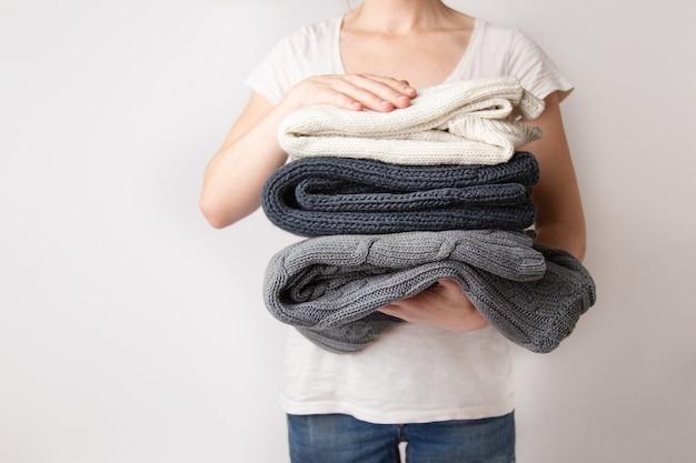 Dziewczyna trzyma w dłoniach stos pranych i prasowanych ubrań z dzianinowych swetrów