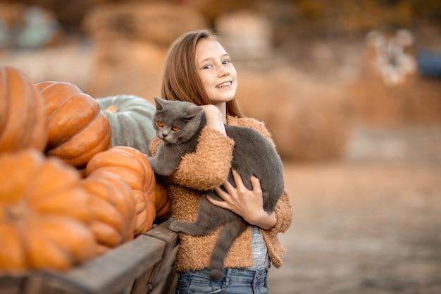 Dziewczyna trzyma w ramionach czarnego kota.