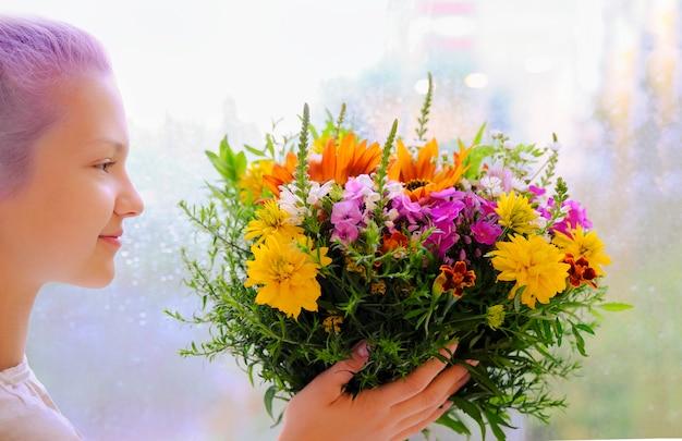 Dziewczyna trzyma w rękach bukiet polnych kwiatów. krótka fryzura. liliowe włosy.