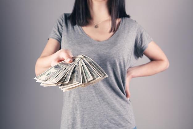 Dziewczyna trzyma w rękach duże pieniądze