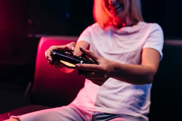 Dziewczyna trzyma w rękach gamepad i grając w gry wideo