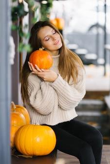 Dziewczyna trzyma w rękach jesienną dynię, ciesząc się jesiennym słonecznym dniem
