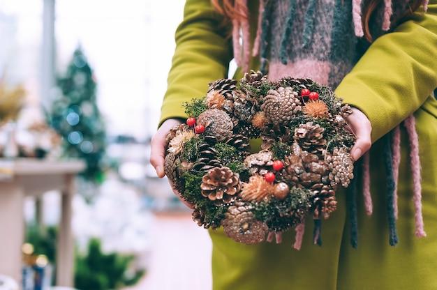 Dziewczyna trzyma w rękach noworoczny, świąteczny wieniec z ozdobnych ozdób do domu