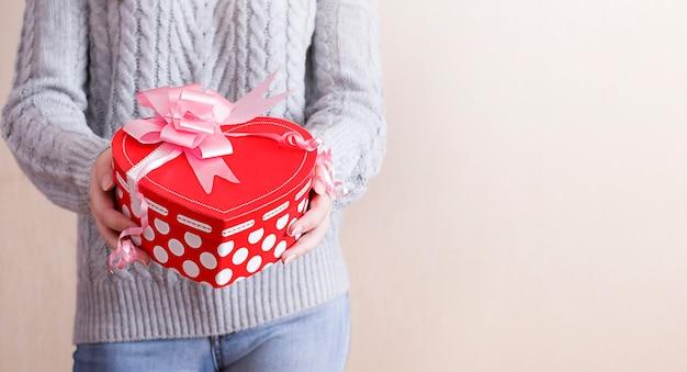 Dziewczyna trzyma w rękach prezent w kształcie serca