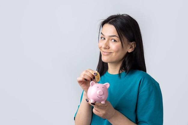 Dziewczyna trzyma w rękach różową skarbonkę i monetę. pojęcie bogactwa i akumulacji.
