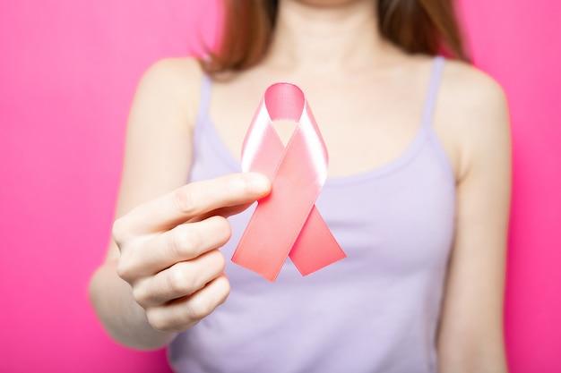 Dziewczyna trzyma w rękach różową wstążkę. symbol raka piersi