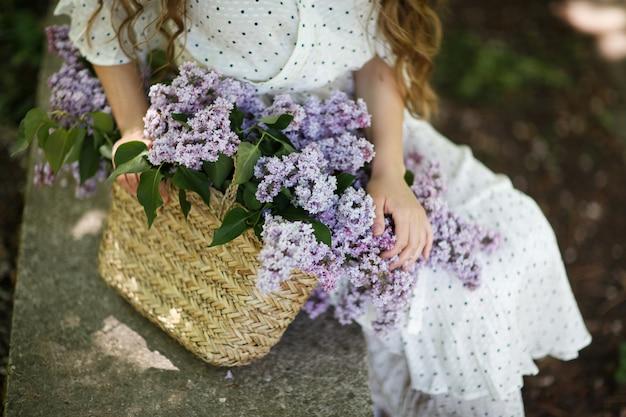 Dziewczyna trzyma w rękach wiklinowy kosz z kwiatami. kosz z bzami. dziewczyna i kwiaty. spacer z koszem bzu w rękach. florystyka. przytulna atmosfera ze świeżymi, pachnącymi kwiatami.