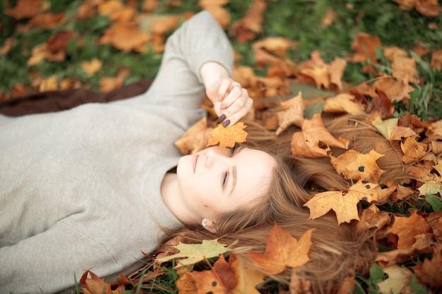 Dziewczyna trzyma w ręku liść klonu nad kolorowymi opadłymi liśćmi w tleprzytulna jesień
