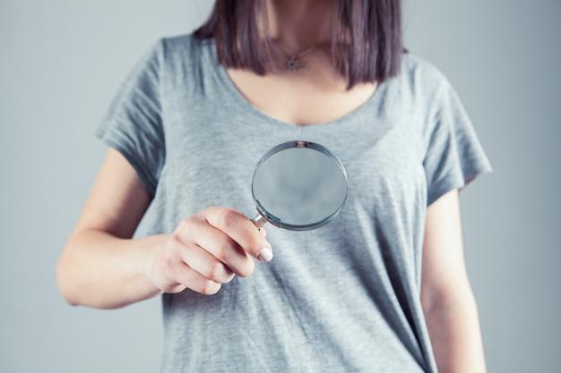 Dziewczyna trzyma w ręku lupę i szuka