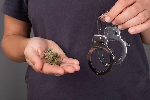 Dziewczyna trzyma w ręku pączek marihuany i kajdanki